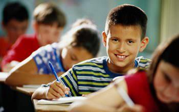 Children writing in classroom (focus on boy in center)   Original Filename: 200141848-002.jpg
